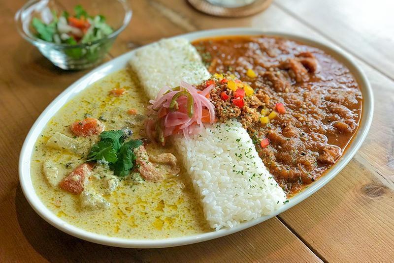 spiceスエヒロの3種の鶏のチキンカレーと海老と野菜のグリーンカレーのあいがけの写真